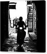 a scooter rider in the back light in a narrow street in Italy Canvas Print