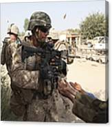 A U.s. Marine Gives A Piece Of Candy Canvas Print