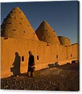 A Woman Walks Past A Sunlit Mud Brick Canvas Print