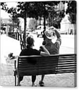 Couple Resting On A Downtown Bench On A Windy Day Canvas Print