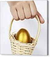 Girl's Hand Holding Basket With Golden Egg Canvas Print
