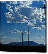 Silhouetted Telephone Poles Under Puffy Canvas Print