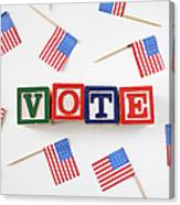 Studio Shot Of Small American Flags And Wooden Blocks With Text Vote Canvas Print
