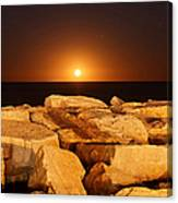 The Moon Rising Behind Rocks Lit Canvas Print