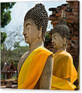 Two Buddha Statues Wrapped In An Orange Scarf  Canvas Print