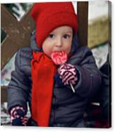 Baby In Red Hat Sits On A Bench In The Street With Candy Canvas Print
