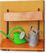 A Watering Can Of  Aluminium And A Plastic One Laid On Wooden Bench Canvas Print