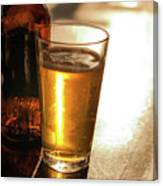 Backlit Glass Of Beer And Empty Bottle On Table Canvas Print