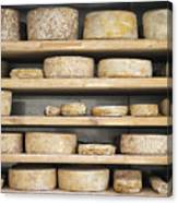 Cheese Wheels On Wooden Shelves In The Cheese Store Canvas Print