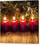 Glowing Red Candles With Snow Covered Evergreen Branch On Rustic Canvas Print