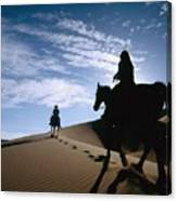 Horseback Riders In Silhouette On Sand Canvas Print