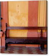 Long Wooden Bench Against A Yellow Wall At The Alcazar Of Seville Canvas Print
