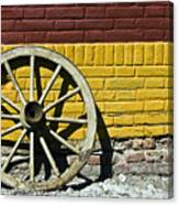 Old Wooden Wheel Against A Wall Canvas Print