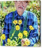 Senior Gardener Showing A Potted Flower. Canvas Print