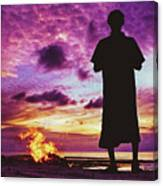 Silhouette Of A Local Man Standing By The Bonfire On The Beach In Maldives During Dramatic Sunset Canvas Print