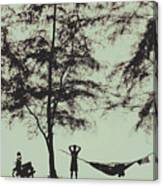 Silhouette Of A Young Men With Crossed Hands Above His Head Camping Hammocking In The Nature Canvas Print