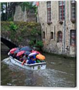 Tourists With Umbrellas In A Sightseeing Boat On The Canal In Bruges Canvas Print