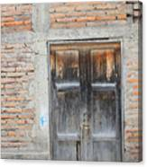 Weathered Wood Door In An Adobe Brick Wall Canvas Print