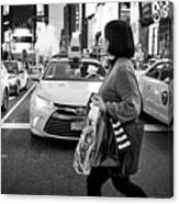 woman crossing crosswalk in front of yellow cabs in the evening in Times Square New York City USA Canvas Print