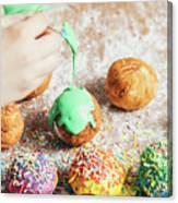 Woman's Hand Coating A Donut With Green Frosting. Canvas Print
