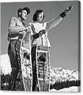 Couple Holding Snowshoes, Woman Pointing Canvas Print