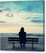 Man In Hood Sitting On A Lonely Bench On The Beach Canvas Print