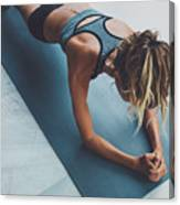 Sporty woman doing exercise in a gym Canvas Print