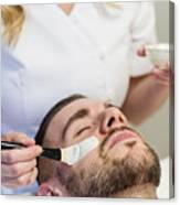 Young man receiving a facial treatment in beauty spa. Canvas Print