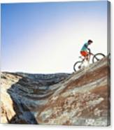 A man riding a mountain bike on an extreme sandstone ledge Canvas Print