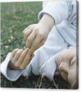 Boy Lying On Grass Holding Fingers Together In Front Of Face Canvas Print
