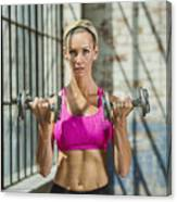 Caucasian woman lifting weights in warehouse Canvas Print