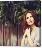 Caucasian woman standing under leaves by fence Canvas Print