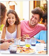Family gathered at an outdoor restaurant to share a meal Canvas Print