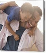 Mixed race father and son playing on sofa Canvas Print