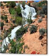 Waterfall between red sandtsone rocks in a desert landscape Canvas Print