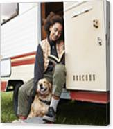 Woman with dog reading book in motor van Canvas Print