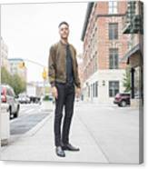 Young man standing on city sidewalk Canvas Print