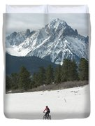 A Woman Bike Riding On The  Snow Duvet Cover