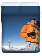 Dressed In Orange, A Skier Sips A Warm Duvet Cover