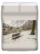 Park Bench In The Snow Covered Park Overlooking Lake Duvet Cover