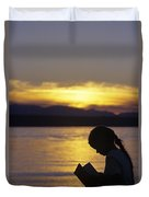 Young Girl Silhouetted Reading A Book On The Beach At Sunset Duvet Cover