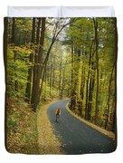 Biker On Road Amidst Fall Foliage Duvet Cover