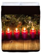 Glowing Red Candles With Snow Covered Evergreen Branch On Rustic Duvet Cover