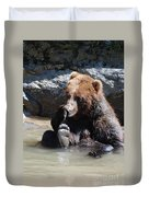 Grizzly Bear Licking His Paw While Seated In A Muddy River Duvet Cover