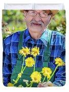Senior Gardener Showing A Potted Flower. Duvet Cover