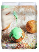 Woman's Hand Coating A Donut With Green Frosting. Duvet Cover