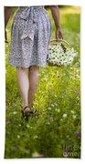 Woman Walking Through A Wild Flower Meadow With A Basket Of Flow Bath Towel
