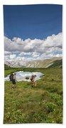 A Couple Hiking Through A Field Bath Towel