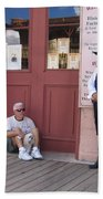 A Dog And A Re-enactor Rest In The Front Of The Bird Cage Theater Tombstone Arizona Bath Towel