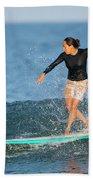 A Woman Rides A Wave On A Longboard Bath Towel